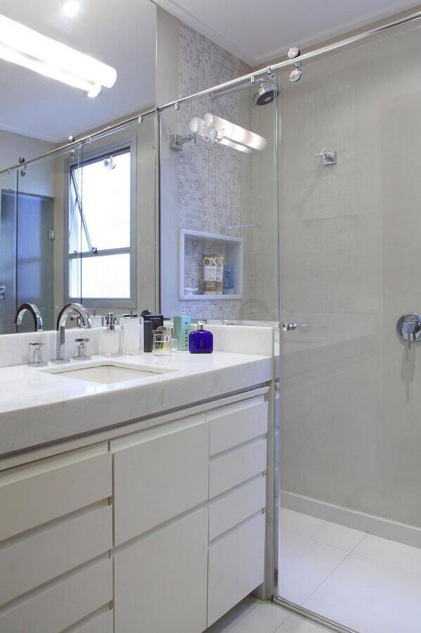 banheiro pequeno planejado com armário branco e box de vidro Foto Cris Paola Arquitetura