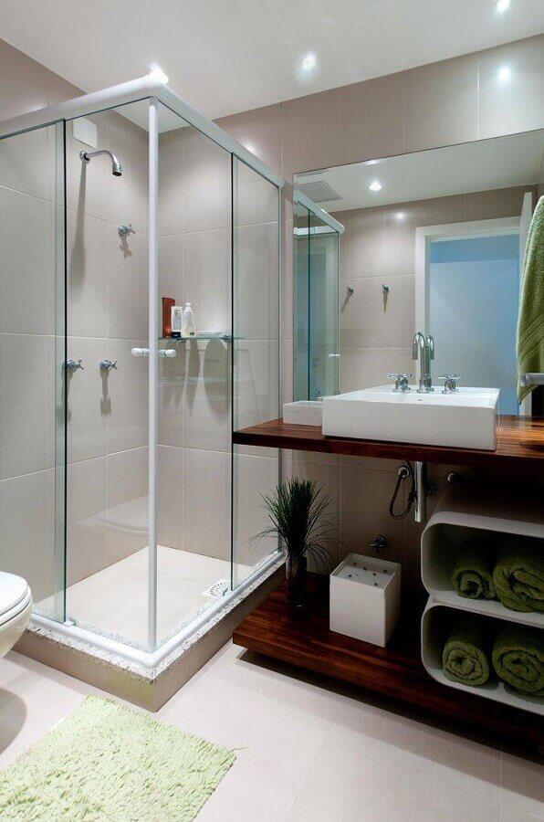 decoração de banheiro pequeno com bancada de madeira e box de vidro Foto ArchDesign Studio