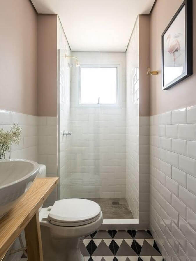 decoração simples de banheiro pequeno branco e rosa com piso hidráulico e bancada de madeira Foto Aaron Guides