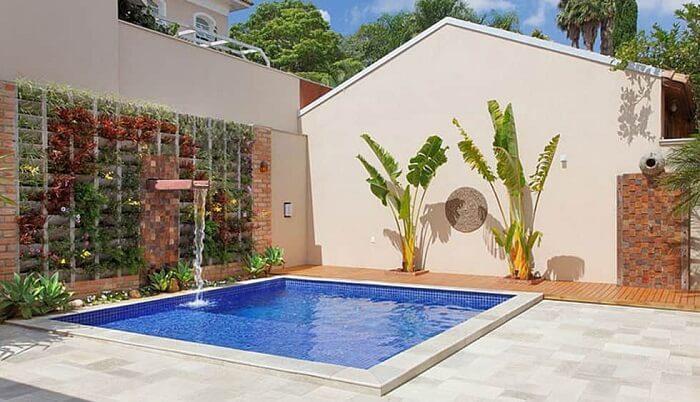 Área de lazer pequena com piscina e jardim vertical