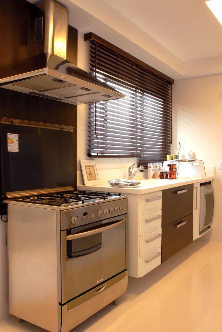 Cozinha pequena decorada com paredes, piso e móveis em tons claros