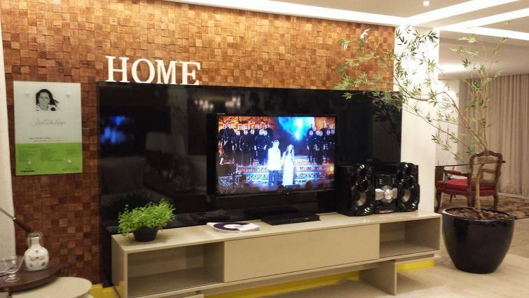 sala pequena com painel de TV e rack