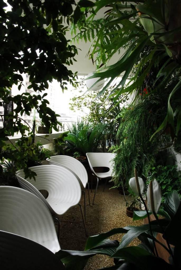 Jardim externo com cadeiras brancas