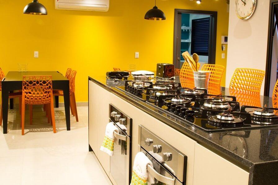 Bancada de cozinha em pedra preta dando destaque às cores das cadeiras e parede Projeto de Abreu Coimbra Arquitetura