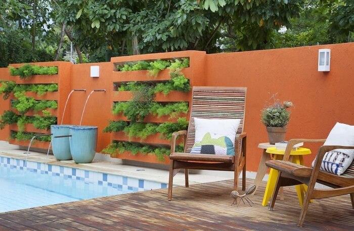 Casa com muro laranja, piscina e jardim vertical