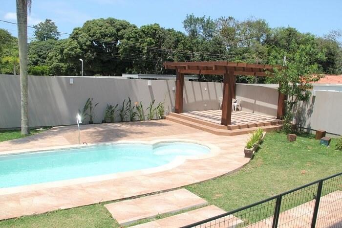Casas com piscinas com pergolado de madeira