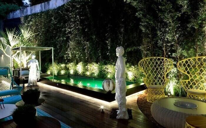 Casas com piscinas iluminadas com deck de madeira