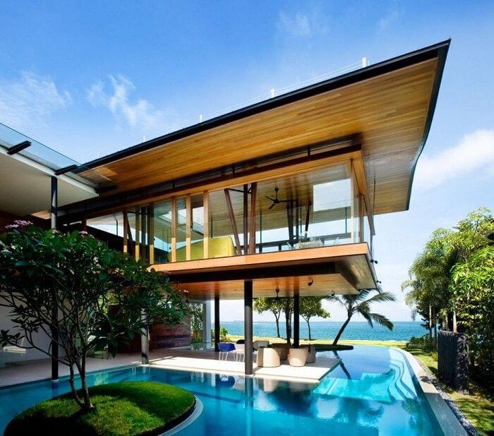 Casas com piscinas, teto revestido com madeira e ilha com grama verde