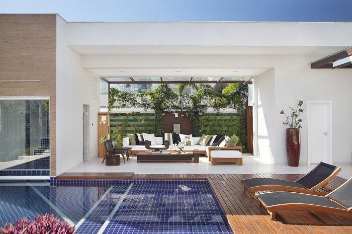 Varanda com jardim vertical integrada a piscina
