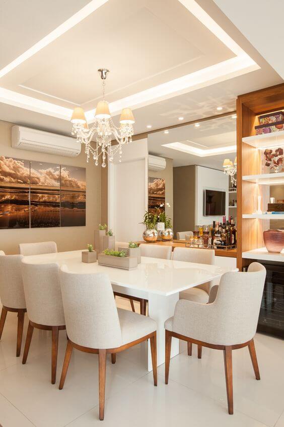 Rebaixamento de gesso na sala de estar com lustre clássico no centro