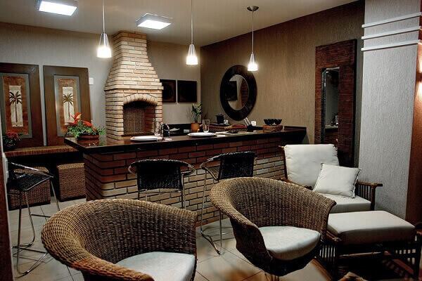 Área de churrasco com cadeira, churrasqueria e luminárias