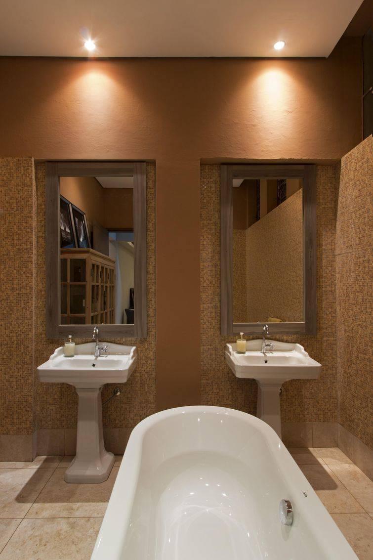 Banheiro com pastilhas marrons seguindo a paleta de cores do ambiente