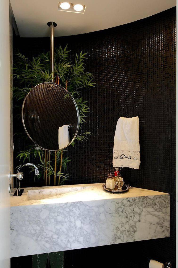 Banheiro com parede de pastilhas pretas brilhantes