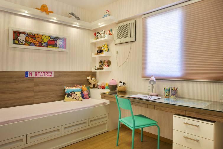 Quarto feminino com abajur infantil sobre a escrivaninha