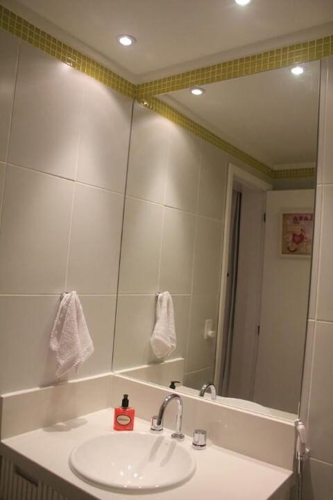 Banheiros decorados com pastilhas amarelas em faixa próxima ao teto Projeto de BL Arquitetura