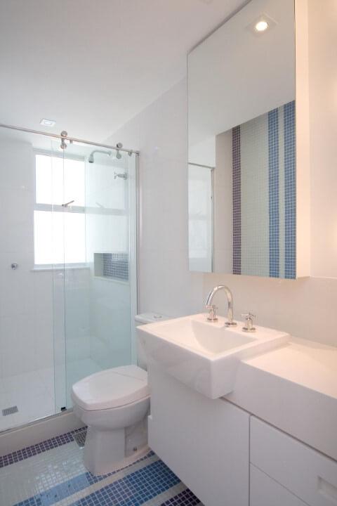 Banheiros decorados com pastilhas azuis em faixas no chão e parede Projeto de Juliana de Sá