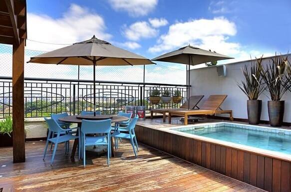 Deck de piscina pequena e espreguicadeiras e mesa com ombrelone Projeto de Studio Scatena