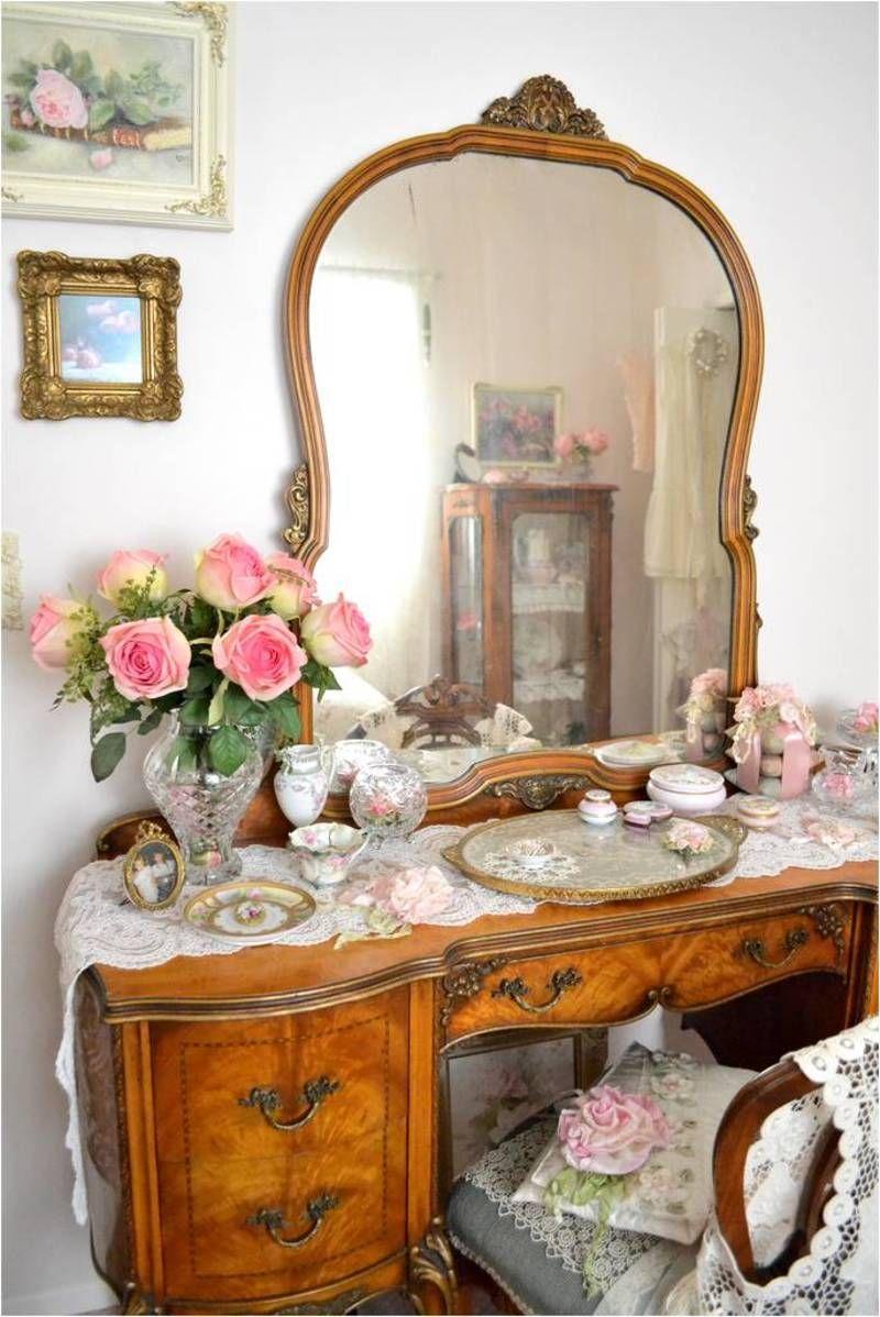 Penteadeira antiga de madeira e flores cor de rosa