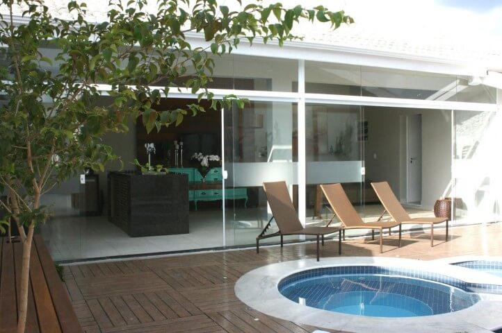 Piscina com pisos que imitam madeira Projeto de Mariana Campos