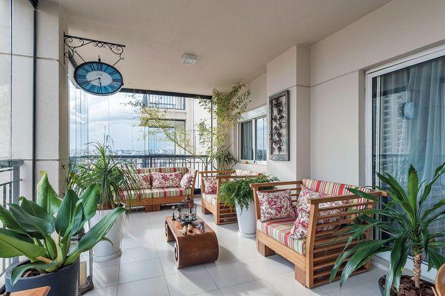 Plantas para apartamento - varanda com sofá e poltronas de madeira