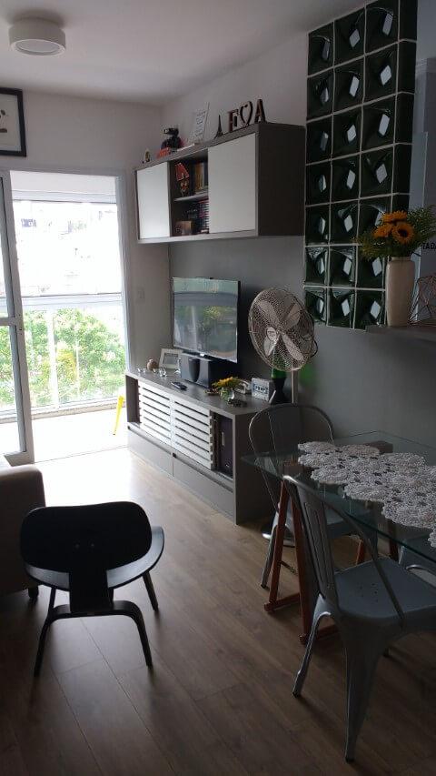 Sala de estar com pisos que imitam madeira Projeto de Audrey Migliani
