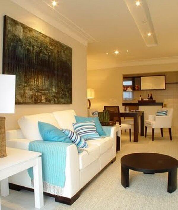 Teto de gesso e sofá com almofadas azuis