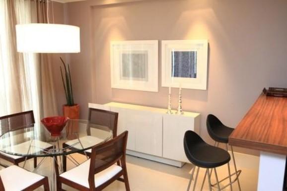 Mesa redonda de vidro com base metálica e cadeiras de madeira