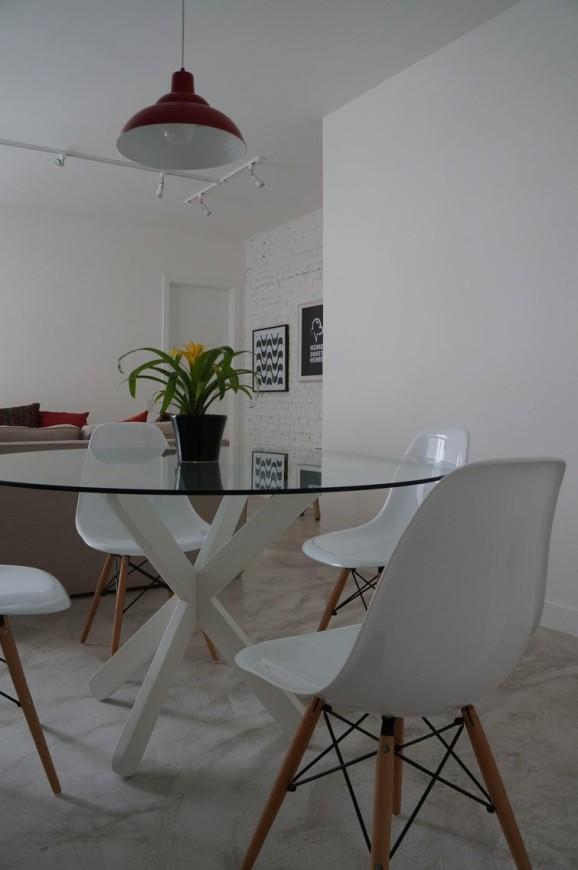 Mesa redonda de vidro com base branca e cadeiras Eames Projeto por Pmartino Arquitetura e Decoração
