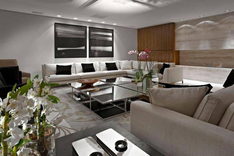 Sofás de canto na cor branca com detalhes escuros deixa o ambiente mais elegante