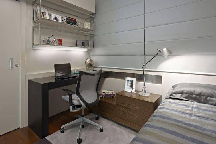 Quarto decorado com mesa para computador preta e criado mudo castanho