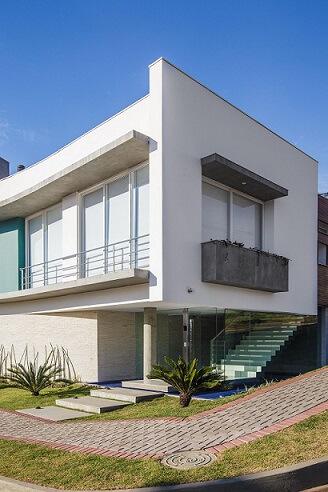 Casa branca com detalhes em cimento queimado e telhado embutido Projeto de Grupo PR Arquitetura