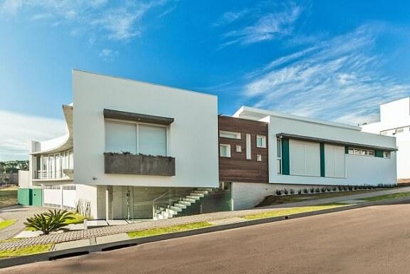 Casa branca com madeira e telhado embutido Projeto de Grupo PR Arquitetura