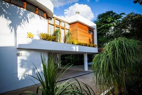 Casa branca com madeira e telhado embutido Projeto de Mascarenhas Arquitetos