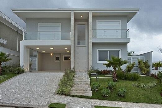 Casa cinza com revestimento de pedra e telhado embutido Projeto de Guardini Stancati