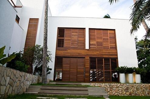 Casa com portas de madeira e telhado embutido Projeto de Renato Teles Arquitetura