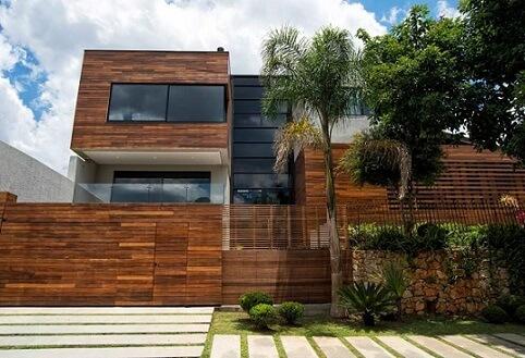 Casa com revestimento em madeira e telhado embutido Projeto de Elmor Arquitetura