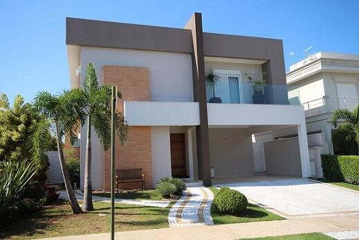 Casa com telhado embutido e detalhe de tijolos aparentes