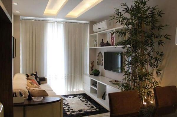 O rack e as prateleiras que fazem parte da decoração de sala pequena se encaixam perfeitamente no ambiente