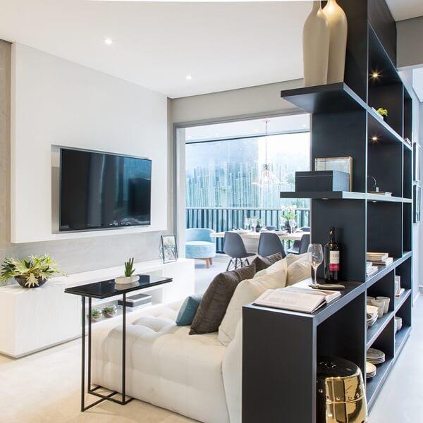 A estante atrás do sofá agrega valor e funcionalidade na decoração de sala pequena