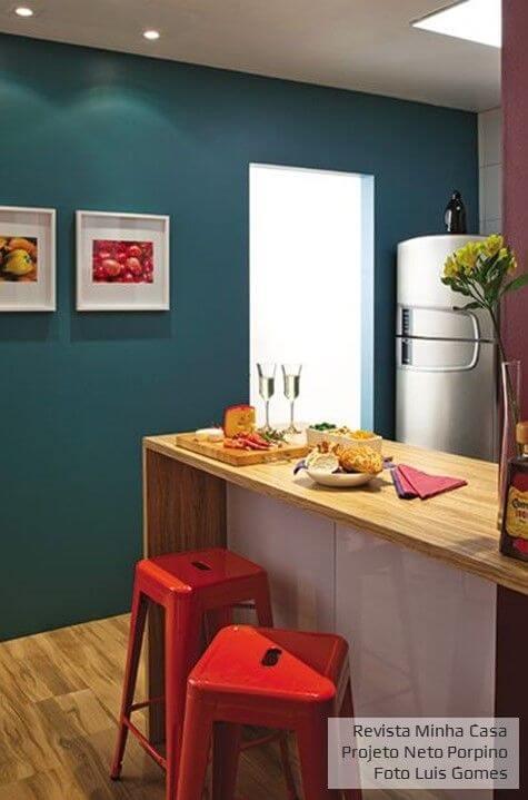Cozinha colorida com parede azul e bancos vermelhos Projeto de Neto Porpino