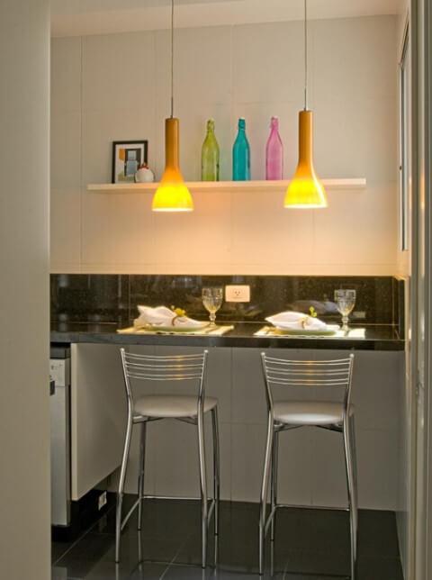Cozinha colorida com pendentes e garrafas coloridas Projeto de Diptico