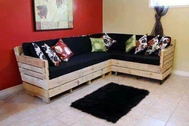 Sofá de palete com almofadas pretas e estampadas