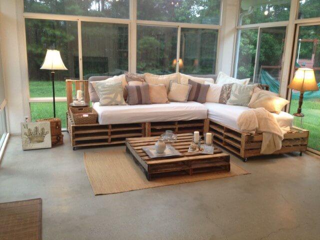 Sofá de palete com mesa de centro de pallet em sala iluminada