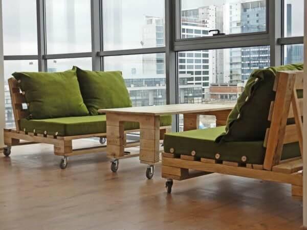 Sofá de palete com rodinhas e almofadas verdes