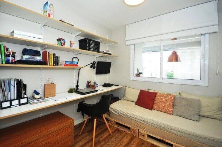 Sofá de palete em quarto com muitas prateleiras