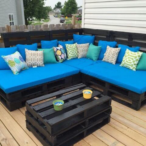 Sofá de palete escuro com almofadas azuis