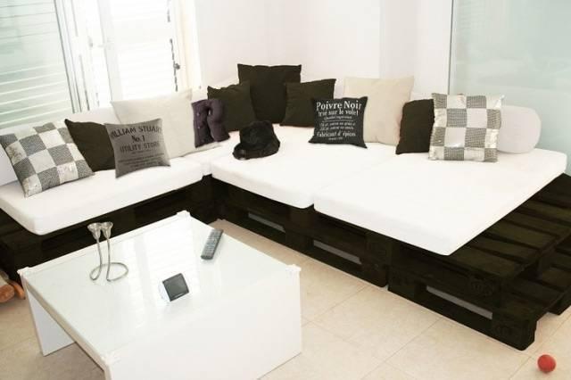 Sofá de palete em cor escura com almofadas claras