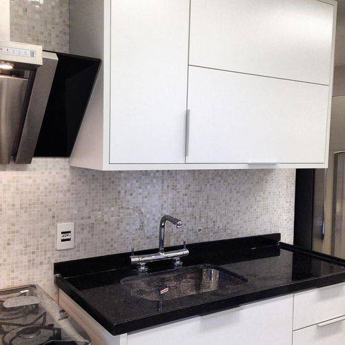 Cozinha compacta com armários brancos contrastando com o balcão de granito preto Projeto de Iago Patucci