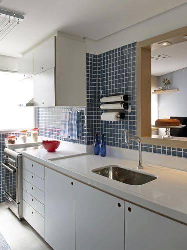 Cozinha compacta com revestimentos azuis e bancada branca Projeto de Marina Carvalho