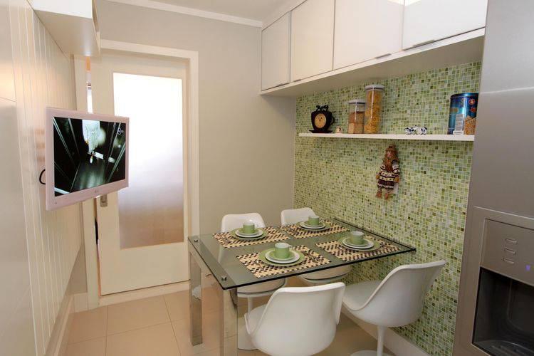 Cozinha compacta e moderna com mesa de vidro e armários brancos Projeto de Lorrayne Zucolotto